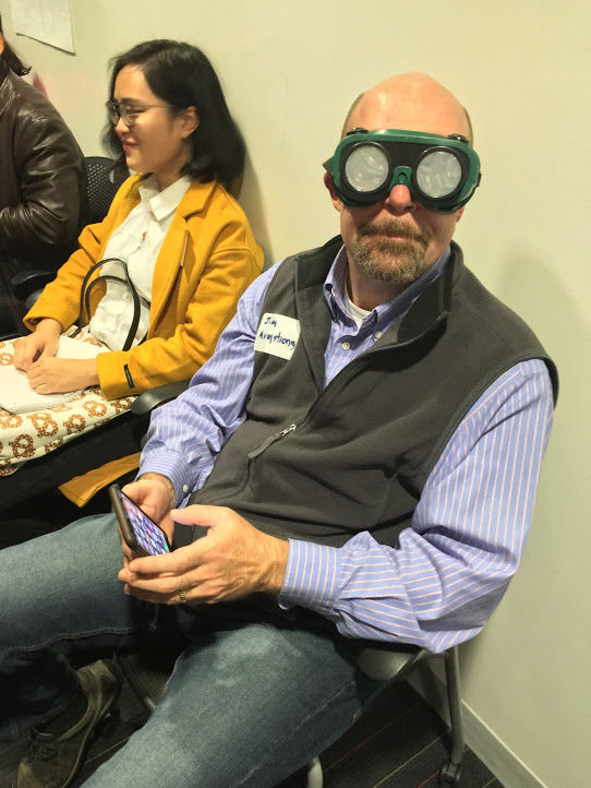 Participant in the Inclusive Design Thinking workshop trying on the low vision goggles.