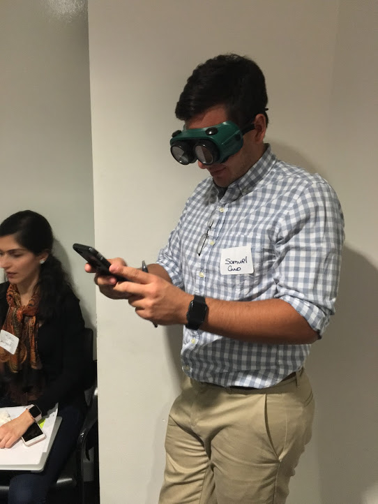 Samuel Cano, WPI 2016, tries to read his phone wearing low vision goggles.
