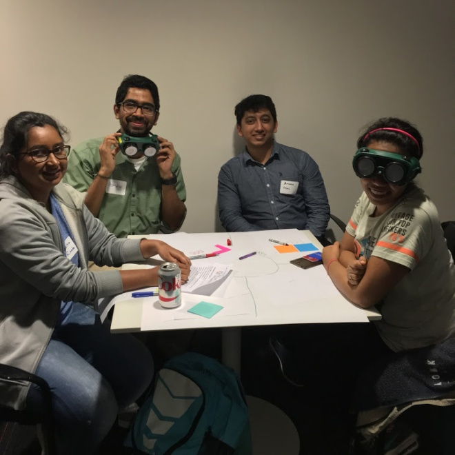 WPI students try on low vision goggles while planning their empathy map.